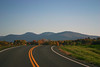 A remote country road cuts through the mountains in the late fall waning sunlight
